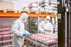 Factory employees unloading packs of bottles. Sports nutrition production employees in protective clothing unloading packs of plastic bottles in warehouse stock photography