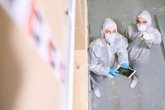 Storage worker pointing to colleague with tablet. Sports nutrition production worker standing in warehouse in protective clothing and indicating something to stock photo