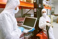 Storage worker using laptop. Sports nutrition production worker standing in warehouse in protective clothing and using laptop computer royalty free stock photos