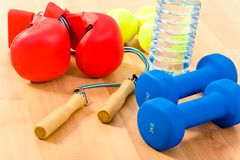 Sports objects. Photo of two blue barbells, some tennis balls, bottle of water and boxing gloves on wooden surface Stock Images