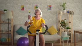 Sports old woman in headphones engaged in cardio training on a exercise bike drinking water from a bottle. Active sports senior woman in headphones engaged in stock footage