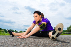 Sports outdoor - young woman doing fitness in park Royalty Free Stock Photography
