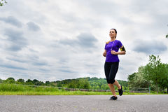 Sports outdoor - young woman running in park Royalty Free Stock Photo