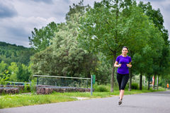Sports outdoor - young woman running in park. Urban sports - Woman running for better fitness in the city park on a cloudy summer day Stock Image