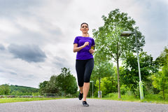 Sports outdoor - young woman running in park. Urban sports - Woman running for better fitness in the city park on a cloudy summer day Stock Photos