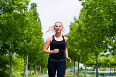 Sports outdoor - young woman running in park. Urban sports - woman running for better fitness in the city park on a cloudy summer day Royalty Free Stock Image