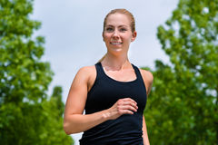 Sports outdoor - young woman running in park. Urban sports - woman running for better fitness in the city park on a cloudy summer day Royalty Free Stock Photos