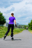 Sports outdoor - young woman skating in park. Urban sports - woman skating with Roller blades for better fitness in the city park on a cloudy summer day Royalty Free Stock Photos
