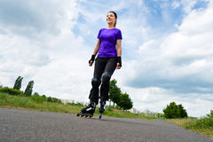 Sports outdoor - young woman skating in park. Urban sports - woman skating with Roller blades for better fitness in the city park on a cloudy summer day Stock Image