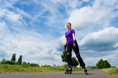 Sports outdoor - young woman skating in park. Urban sports - woman skating with Roller blades for better fitness in the city park on a cloudy summer day Stock Photo
