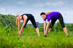 Sports outdoor - young women doing fitness in park Stock Images