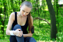 Sports Park. Sportswoman bended knee because of an ankle painful sprain injury. Female runner athlete lesion royalty free stock image