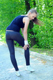Sports Park. Sportswoman bended knee because of an ankle painful sprain injury. Female runner athlete lesion stock photo