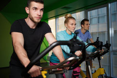 Sports people on stationary bike Stock Photography