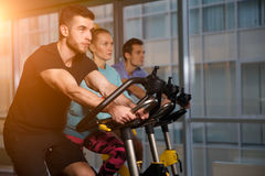 Sports people on stationary bike Royalty Free Stock Images