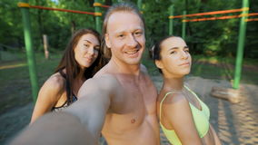 Sports people after trenerovki. Two girls and one man, do not selfie phone. They are located in the park on the playground stock footage