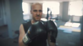 Sports and people, young male athlete training in boxing gym. Beats his fists at the camera. On the hands of boxing. Gloves stock video footage