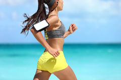 Sports phone armband fitness runner exercising on beach - cardio workout. Sports phone armband fitness jogger exercising on beach - cardio workout. Midsection royalty free stock images