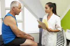 Sports Physiotherapist Treating Male Client Royalty Free Stock Images