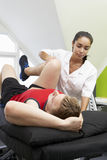 Sports Physiotherapist Treating Male Client Stock Images