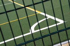 Sports pitch. White and yellow line markings on sports pitch viewed through metal fence stock image