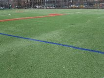 Sports field with no players, red and green lines. Sports play area for soccer and baseball. Bright green artifical turf. Open empty, absent athletes. Urban stock images