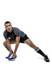 Sports player in black jersey stretching with ball Stock Images