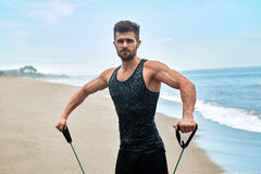Sports. Portrait Of Man Exercising At Beach During Outdoor Workout. Sports. Portrait Of Handsome Male Doing Expander Exercise During Outdoor Workout At Sea. Fit Royalty Free Stock Images
