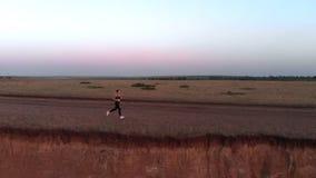 Sports pulsant au coucher du soleil, une fille dans des écouteurs fonctionnant le long d'une falaise raide banque de vidéos