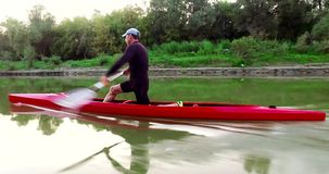 Sports rowing on the kayak. The man floats down the river along the wood.  stock video