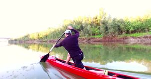 Sports rowing on the kayak. The man floats down the river along the wood.  stock footage