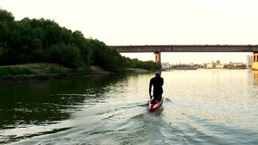 Sports rowing on the kayak. The man floats down the river along the wood. Slow motion stock footage