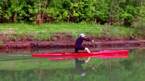 Sports rowing on the kayak. The man floats down the river along the wood. Slow motion stock video footage