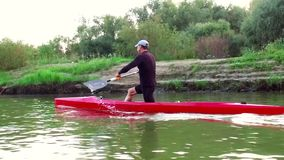 Sports rowing on the kayak. The man floats down the river along the wood. Slow motion stock video