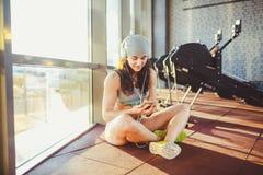 Sports, santé et technologie de thème la belle sportive caucasienne sexy de femme dans les vêtements de sport et le chapeau gris  Image stock