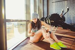 Sports, santé et technologie de thème la belle sportive caucasienne sexy de femme dans les vêtements de sport et le chapeau gris  Photographie stock libre de droits