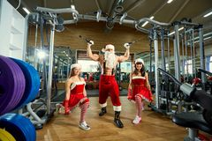 Sports Santa Claus with girls in Santa`s costumes in the gym. Sports Santa Claus with girls in Santa`s costumes in the gym on Christmas and New Year royalty free stock images