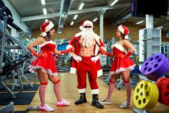 Sports Santa Claus with girls in Santa`s costumes in the gym on. Christmas and New Year royalty free stock images