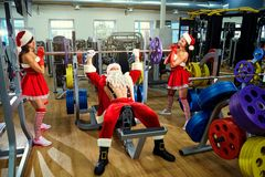 Sports Santa Claus with girls in Santa`s costumes in the gym on. Christmas and New Year royalty free stock photo