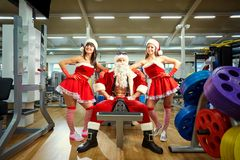 Sports Santa Claus with girls in Santa`s costumes in the gym on. Christmas and New Year stock images