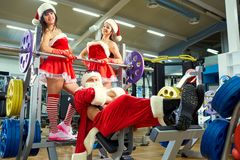 Sports Santa Claus with girls in Santa`s costumes in the gym. Sports Santa Claus with girls in Santa`s costumes in the gym on Christmas and New Year stock photo