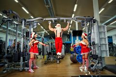 Sports Santa Claus with girls in Santa`s costumes in the gym. Sports Santa Claus with girls in Santa`s costumes in the gym on Christmas and New Year royalty free stock image