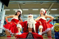 Sports Santa Claus with girls in Santa`s costumes in the gym. Sports Santa Claus with girls in Santa`s costumes in the gym on Christmas and New Year royalty free stock photography