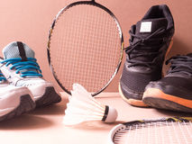 Sports set of black orange sport shoes and blue sport shoe and shuttlecocks with two badminton racket on sport background in conce Stock Photo