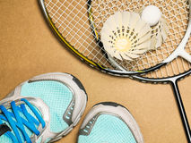 Sports set of blue sport shoes and shuttlecocks with two badminton racket on plywood background Royalty Free Stock Photos