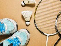 Sports set of blue sport shoes and shuttlecocks with two badminton racket on plywood background Stock Photography