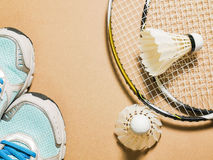 Sports set of blue sport shoes and shuttlecocks with two badminton racket on plywood background Royalty Free Stock Photo
