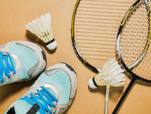 Sports set of blue sport shoes and shuttlecocks with two badminton racket on plywood background Stock Image