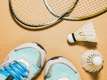 Sports set of blue sport shoes and shuttlecocks with two badminton racket on plywood background Royalty Free Stock Images