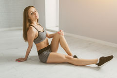 Sports and sexy girl after exercise relaxes in a bright room Stock Images